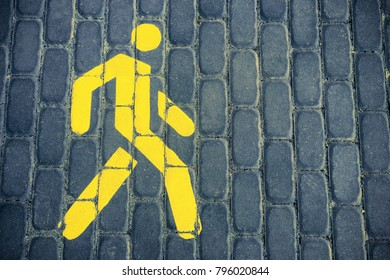 Pedestrian sign. The pedestrian road. The sign is yellow.