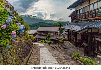 Pedestrian Street Through Historic Wooden Japanese Village on Ancient Trade Highway. Descending Stone Paved Road with Mountain Views in Distance. Summer Day, No People. (Magome, Kiso Valley, Japan).