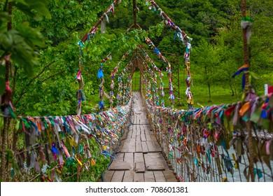 A pedestrian suspension bridge across the river in Abkhazia. Multicolored ribbons are hung on it. Suspension bridge in Abkhazia.