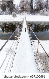 Pedestrian suspension bridge of steel and wood over the river, winter in Russia