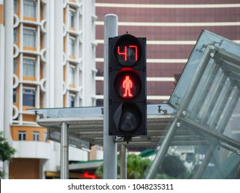 Pedestrian traffic light with countdown timer with a background of modern buildings in urban area. Macau, China.