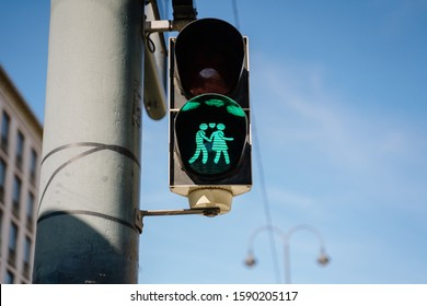 Pedestrian Traffic Lights Original Green Lovers Signal in Vienna, Austria. Lighting Figures Holding Hands with Heart Symbol. Device Hanging on Urban Post. Blurred Building and Blue Sky on Background