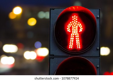 pedestrian traffic lights red on a background of cars and the city at night