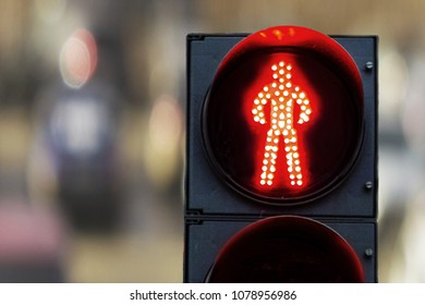 pedestrian traffic lights red on a background of cars and the city at day