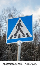 A pedestrian traffic sign frozen in winter