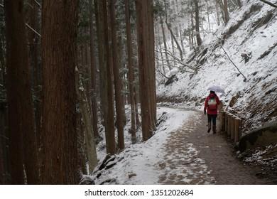 Pedestrian or Traveller walking at Hell Valley, Jigokudani. Landscape of the famous beautiful nature of snow winter in Jigokudani Monkey Park at Yamanouchi in Nagano, Japan.