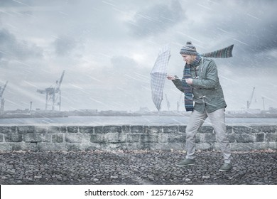 Pedestrian with an umbrella is facing strong wind and rain on a dockside