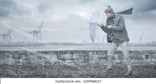 Pedestrian with an umbrella is facing strong wind and rain