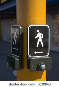 Pedestrian walk button on a yellow pole.