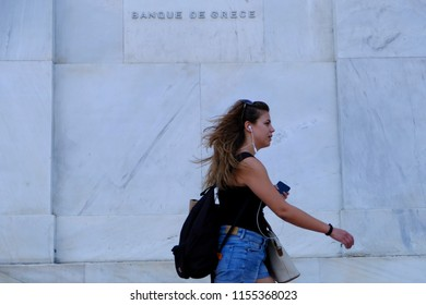 A pedestrian walks in front of a Bank of Greece branch in Athens, Greece on Aug. 13, 2018