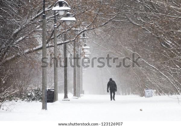 A Pedestrian walks in heavy snow
