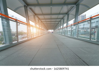 Pedestrian Walkway covered metallic city crosswalk. ground view of corridor interior of pedestrian overpass tunnel with morning sunrise