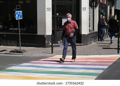 A pedestrian wearing mouth masks walks on a street which was painted into a rainbow flag in Brussels, Belgium on May 15, 2020.