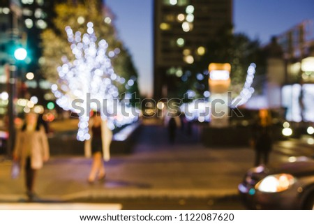 Pedestrians approach a crosswalk in Center City Philadelphia at night. The image is intentionally blurred.
