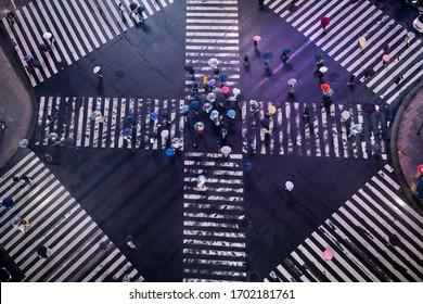 Pedestrians cross Ginza crossing on a wet Autumn night in Tokyo.