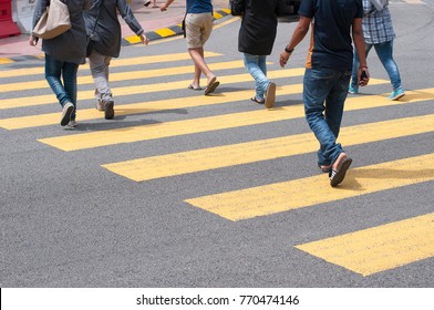 Pedestrians crossing the road using yellow zebra line in Kuala Lumpur, Malaysia