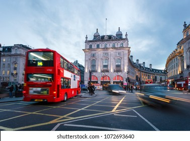 Pedestrians and double-decker buses pass the flashing signs of Piccadilly Circus
