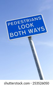 Pedestrians Look both ways warning sign against a clear blue sky background.