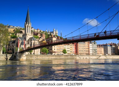 Pedestrians on the Saint Georges footbridge and the Saint Georges church in Lyon, France.