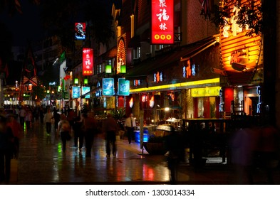 Pedestrians on Zeng Yang Bu Xing Jie street in Guilin China at night with lights of shops and restaurants Guilin, Guangxi, People's Republic of China - October 9, 2011