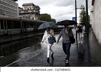 Pedestrians protect theirself from the rain with umbrellas during a rainfall in Brussels, Belgium on May 10, 2016