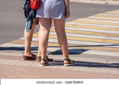 pedestrians waiting to cross the road on sunny summer day