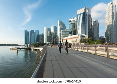 Pedestrians walk along bridge near Marina bay in Singapore with Singapore skyscraper and Merlion park in background