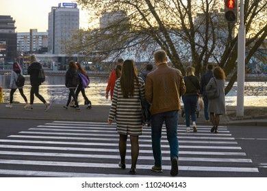 Pedestrians walk along the pedestrian crossing to the red traffic light signal. People from the back cross the road to the prohibiting traffic light signal. Dangerous situation on the street