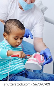 pediatric dentist man shows African boy with dark skin how to properly brush their teeth on a model of the jaw