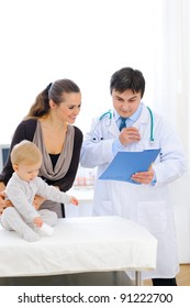 Pediatric doctor talking with mother while baby sitting on table