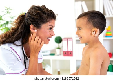 Pediatrician checking the configuration match of the hearing device with her child patient