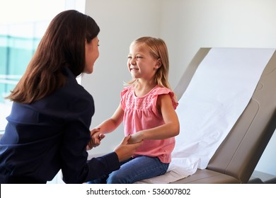 Pediatrician With Child In Exam Room