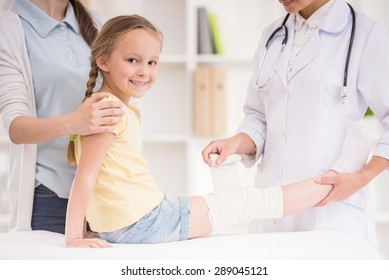 Pediatrician doctor bandaging child's leg. Mother holding baby in her hands.