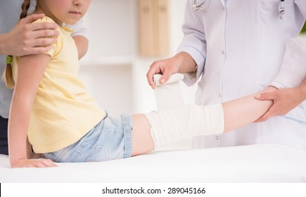 Pediatrician doctor bandaging child's leg. Mother holding baby in her hands. Close-up.