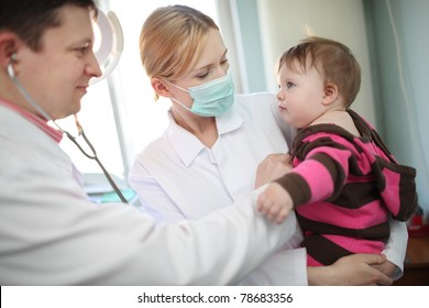Pediatrician doctor examining baby child in clinic.