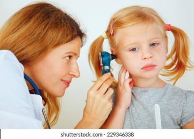 Pediatrician doctor examining little girl's ears.