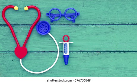 Pediatrician doctor toy accessories including stethoscope, glasses and syringe with copy space