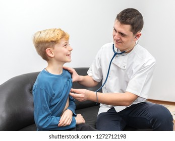 Pediatrician doctor in white uniform with stethoscope listening lung and heart sound of brave and smiling little boy child patient. Stethoscope exam with young resident medic and little kid.