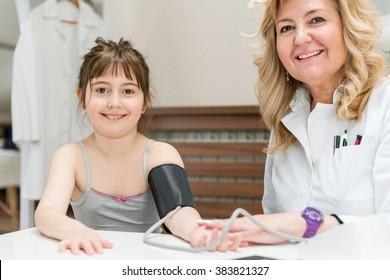 Pediatrician doing medical exam with little girl, measuring blood pressure. Both looking at camera, smiling