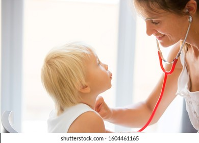 Pediatrician examining baby boy. Doctor using stethoscope to listen to kid and checking heart beat