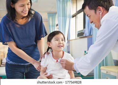 pediatrician examining little girl , her mother beside her