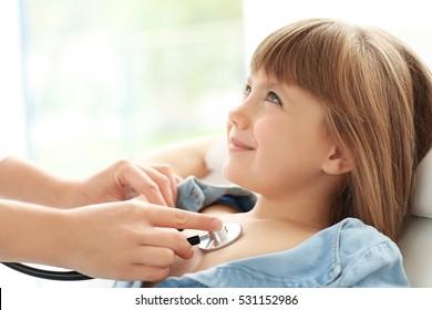 Pediatrician examining little girl's heart