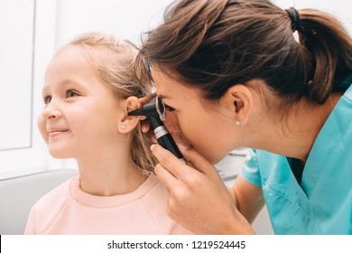 Pediatrician examining little patient with otoscope, hearing exam of child