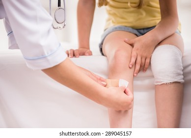 Pediatrician female doctor bandaging child's leg. Close-up.