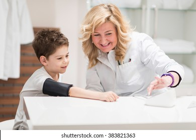Pediatrician with little boy, checking blood pressure, having fun