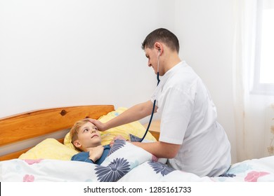 Pediatrician medic and little boy during home visit. Young male doctor visiting little patient at home to consult with stethoscope and diagnose him of cold or fever. Health and medicine concept