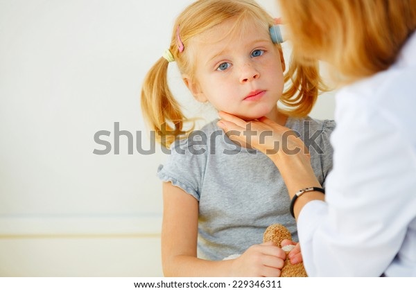 Pediatrician taking temperature with professional thermometer.
