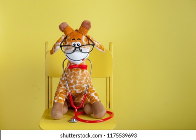 Pediatrician toy animal in glasses with stethoscope isolated on yellow background. Stuffed toy animal giraffe as pediatrician with stethoscope sitting on the chair with copy space.