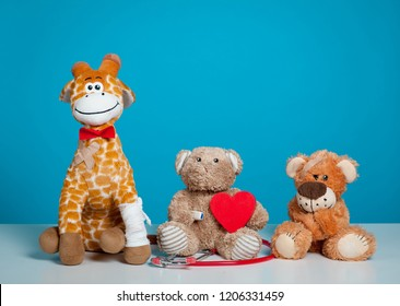 Pediatrician. Toy animal sitting on the chair in hospital isolated on blue background. Health center for children with love. red heart in hands.