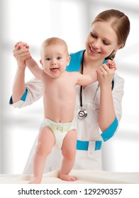 Pediatrician woman doctor holding in his arms baby